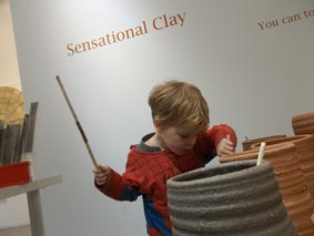 child playing percussion on pottery drum pots made by ceramic artist jon williams