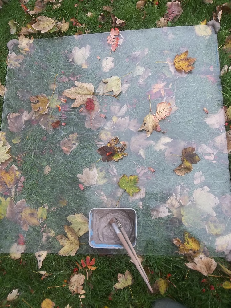clear perspex over laying autumn leaves and designed for messy clay play and outdoor learning for EYFS