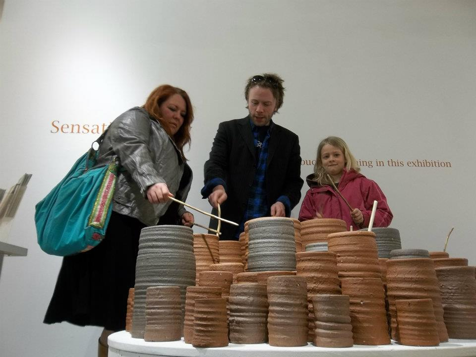 art gallery visitors playing ceramic drum pots by herefordshire ceramic artist jon williams