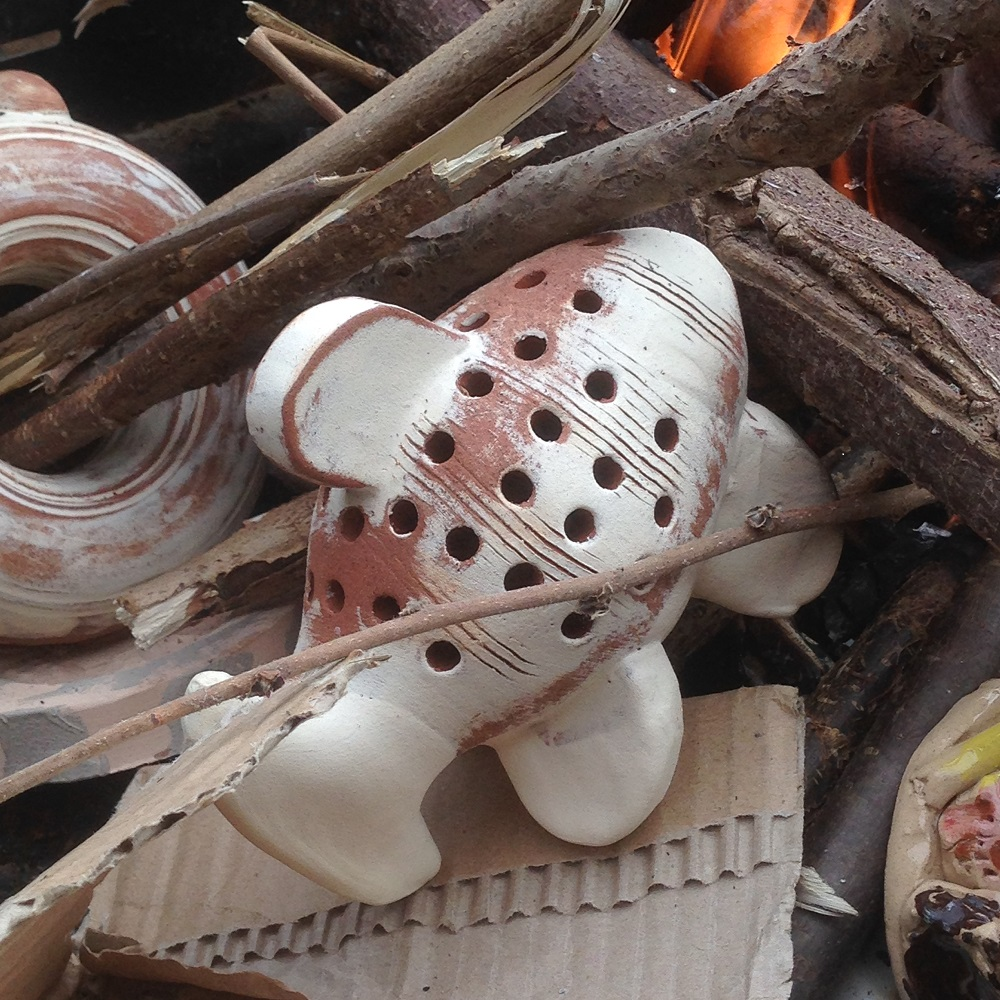 pottery fish and pottery experiments being smoke fired on a bbq