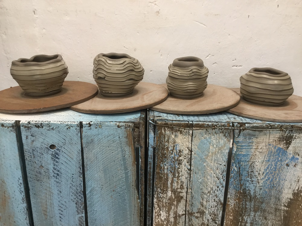 four freshly thrown pots made on the potter's wheel by artist jon williams