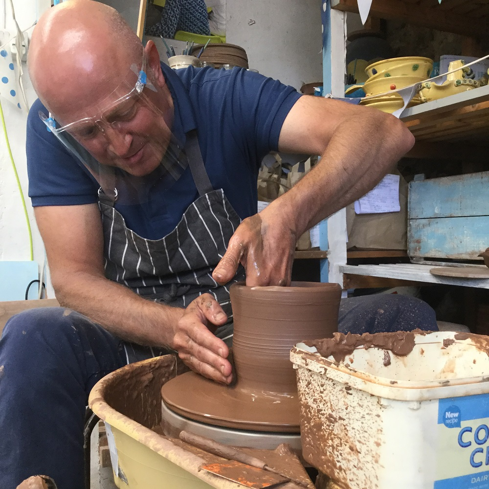potter's wheel course participant makeing a terracotta pot on the pottery wheel at eastnor pottery