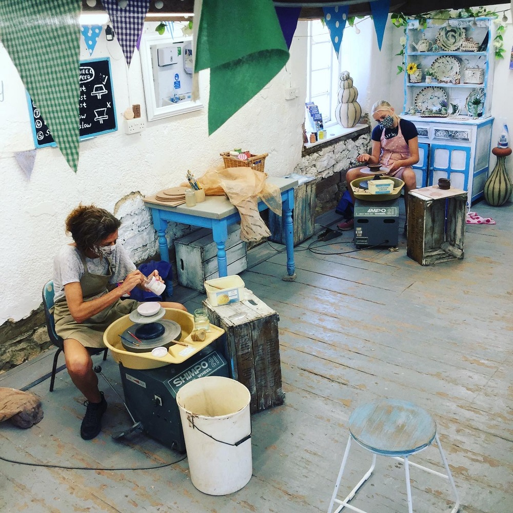 potter's wheel participants taking part in social distanced pottery classes at eastnor pottery in herefordshire
